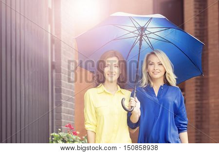 Two attractive young women having an eye contact while walking in the city center with an umbrella.