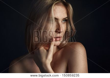 Sensual portrait of girl with freckles touching her lips