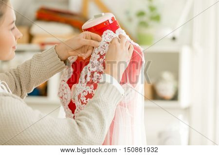 Woman dressing a tailor dummy mannequin in a lace cloth. Concept photo, over a shoulder