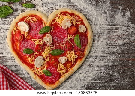 Unbaked pizza in heart shape with ingredients on table