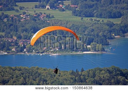 Paraglider flying his wing above Lake Annecy