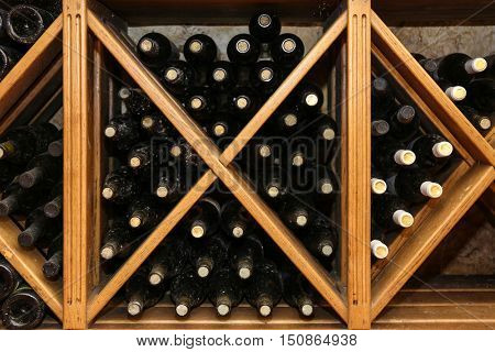 Bottles with wine on wooden shelves in cellar