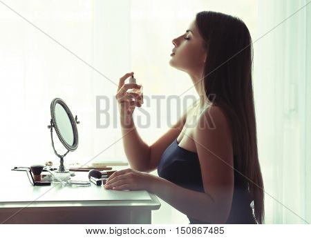 Beautiful young woman looking in mirror while using perfume