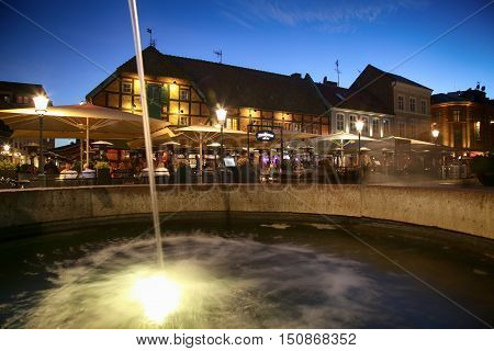 MALMO SWEDEN - AUGUST 16 2016: View of beautiful night scene and fountain on the market place Lilla Torg in Malmo Sweden on August 16 2016.