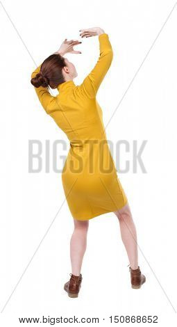 back view woman in a dress protects hands from what is falling from above. Rear view people collection.  backside view of person.  Isolated over white background. Girl in mustard strict dress