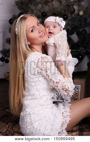 Beautiful Mother Posing With Her Cute Little Baby Girl Beside Christmas Tree