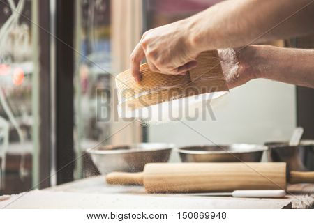 Man preparing dough. Ingredients for baking. Man hands spilling powder on dough. Cooking and baking concept
