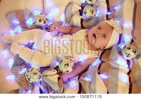 tender photo of small cute baby girl in cozy clothes laying on plaid among Christmas balls