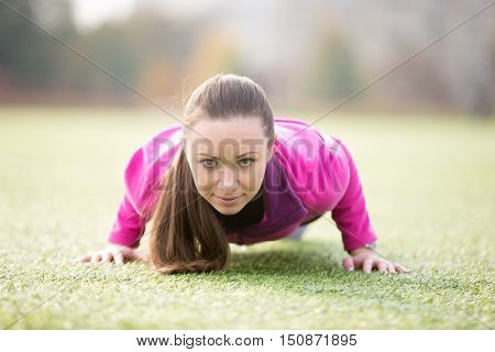 Sporty attractive young woman practicing yoga, doing chaturanga dandasana, push-ups, four-limbed staff posture, working out outdoor on summer day wearing sportswear sweatshirt. Full length, front view
