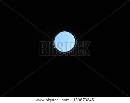 Output is always there. Photo symbolizes that any situation can be find a way out. Through a round hole on a black background can be seen the blue sky.