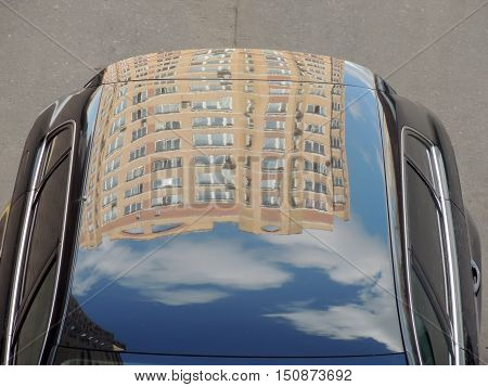 Inverted reflection of the multi-storey residential building on the car roof