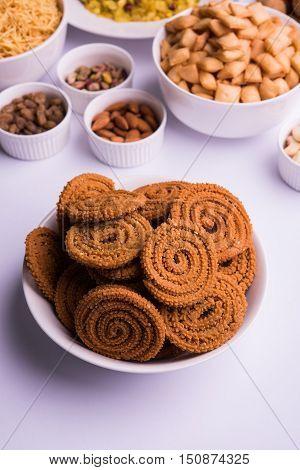 home made tasty Diwali food or Diwali snacks or Diwali sweets like rava laddu, chakli, sev,shankar pale and chivda or chiwada with dry fruits in white bowls, favourite indian diwali recipe