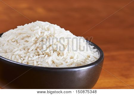 Black Bowl With Rice On A Wood Table