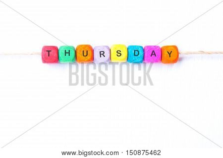 Thursday word of multicolored cubes on a white background
