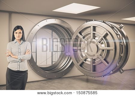 Black haired woman is standing near open bank vault and looking at the viewer. Concept of bank employee.Toned image.