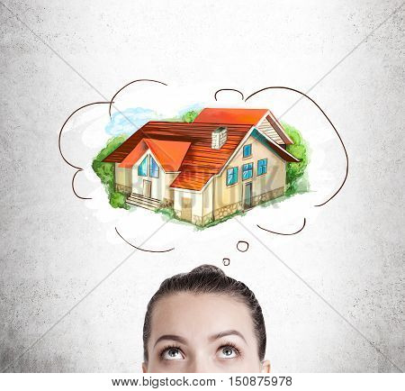 Close up of woman's head dreaming about a new beautiful house of her own. Concept of real estate market