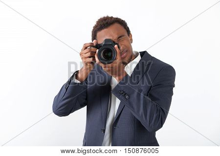 Businessman holding a camera and looking at the viewer and standing against white background. Concept of taking pictures