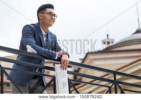 Asian Businessman Holding Newspaper