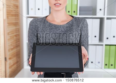 Close up of girl showing a blank tablet screen to the viewer. Concept of marketing and goods promotion. Mock up