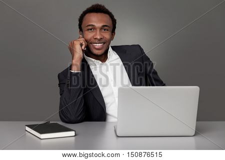 Smiling African American businessman is talking on his phone and looking at the viewer while sitting in office with gray walls and laptop on the table