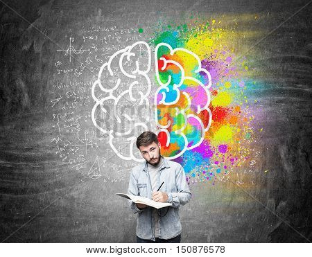 Man with beard and large notebook standing near blackboard with colorful brain picture and formulas. Concept of scientific discovery making