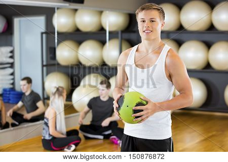 Portrait of confident young man holding medicine ball while friends resting in gym