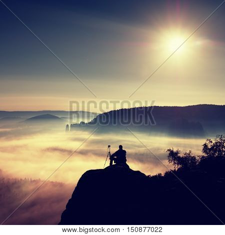 Photographer With Tripod And Camera On Cliff And Thinking. Dreamy Fogy Landscape