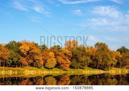 Autumn forest and lake in the fall season. Beautifull sky background