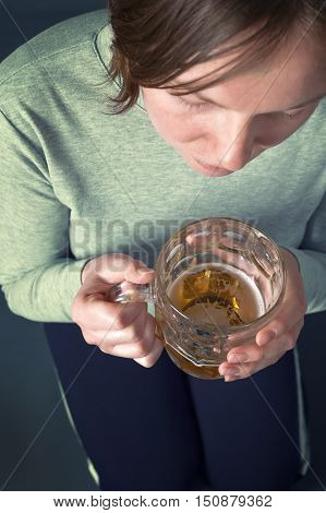 Young girl sitting on floor with light beer from the glass jug. One glass of beer a day concept.