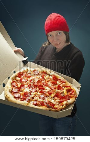 Successful delivery worker woman showing big pizza, selective focus on pizza.