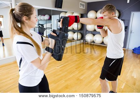 Young male boxer punching bag held by female instructor in health club