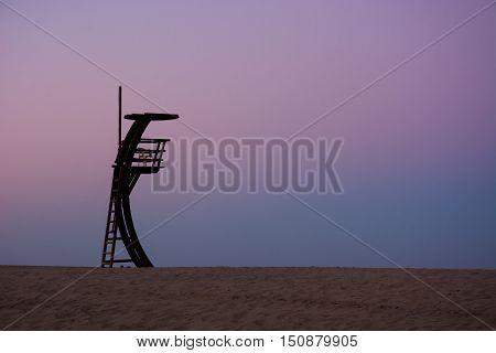 An alone lifeguard tower in an empty beach