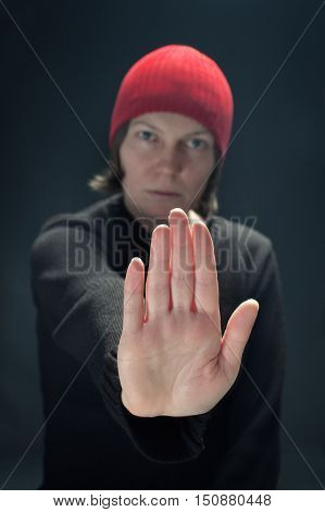 Beautiful woman with red cap showing stop sign low key image. Selective focus on hand.