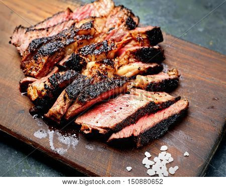 Sliced medium rare grilled Beef steak on wooden cutting board