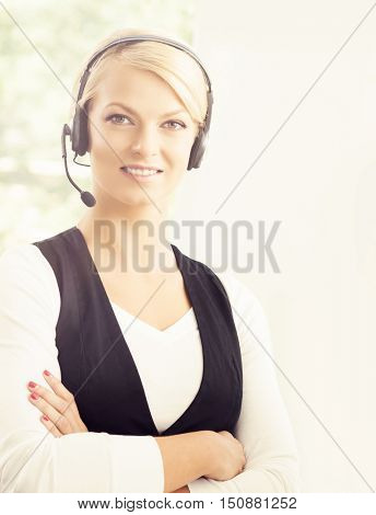 Close-up portrait of support operator at work in a call center. Attractive female office worker. Business concept.
