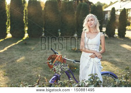 Girl in a white dress with a bicycle walks through the park on a sunny day.