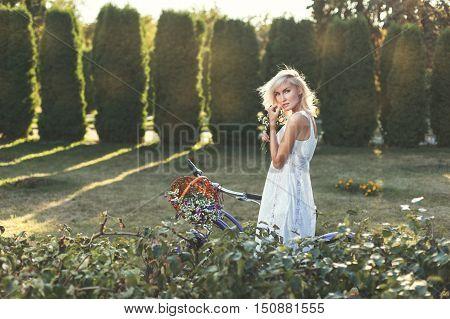 Modest girl in a white dress walks in the park.