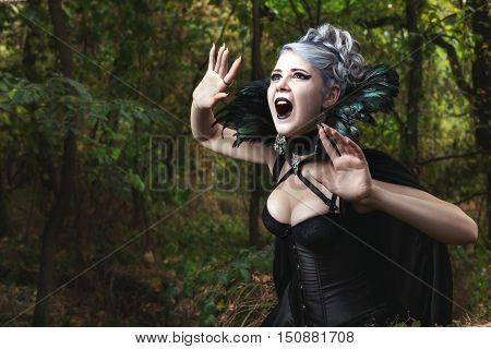 Scary witch screams she gothic clothing and in the woods.