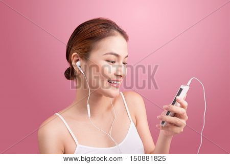 Happy asian girl dancing and listening to the music isolated on a pink background