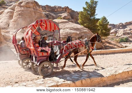 Petra Jordan - November 20 2010. Tourists riding in a horse drawn cart at November 20 2010 in Petra Jordan. Horse-drawn carriages are a great way to get around if you don't feel up to walking and all motorized vehicles are banned.