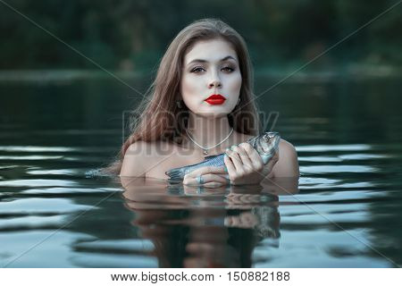 Portrait of a girl in the water with fish trout in the hands.