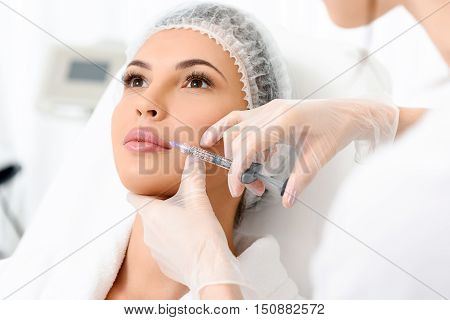 Calm young woman is getting botox treatment. Beautician is injecting liquid near her mouth