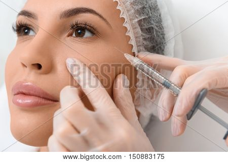 Close up of female face having botox injection at clinic. Woman is looking forward with joy