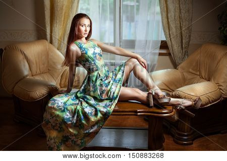 In the room next to the window on the table sits a girl in a dress.