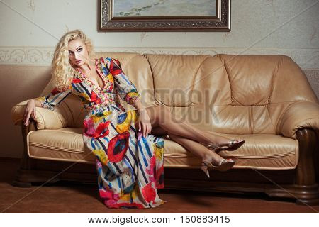 Blonde girl in a bright colored dress sitting on a leather sofa in the room.