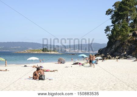BUEU, SPAIN - AUGUST 9, 2016: People having a day in summer in Lapaman beach located between Marin and Bueu in the province of Pontevedra Galicia Spain.