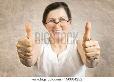 Happy woman showing thumb up.Approval or endorsement concept. Shallow DOF - finger in focus.