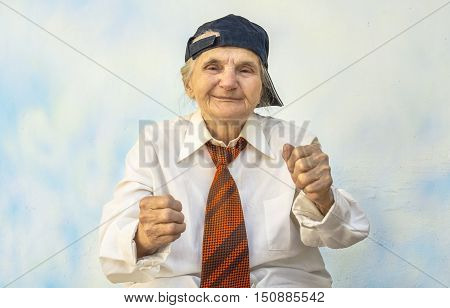 Funny elderly woman supporting something. Selective focus