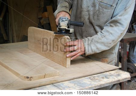 Carpenter polishing a wooden surface, hand and electrical polisher, sanding a plate, polishing wood