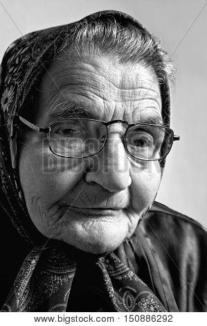 Black and white portrait of an elderly woman. Dreaming the past.